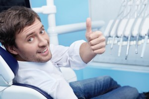 Man happy at the dentist's office thanks to plaque removal and care